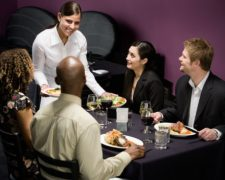 Waitress serving food to table of four adults in restaurant